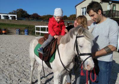 kobieta trzymająca dziecko na koniu prowadzonym przez mężczyznę