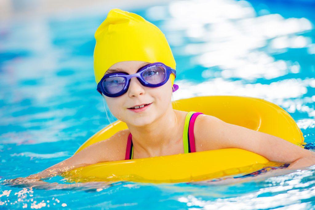 dziecko w czepku i okularkach pływające w basenie przy pomocy dmuchanego koła ratunkowego