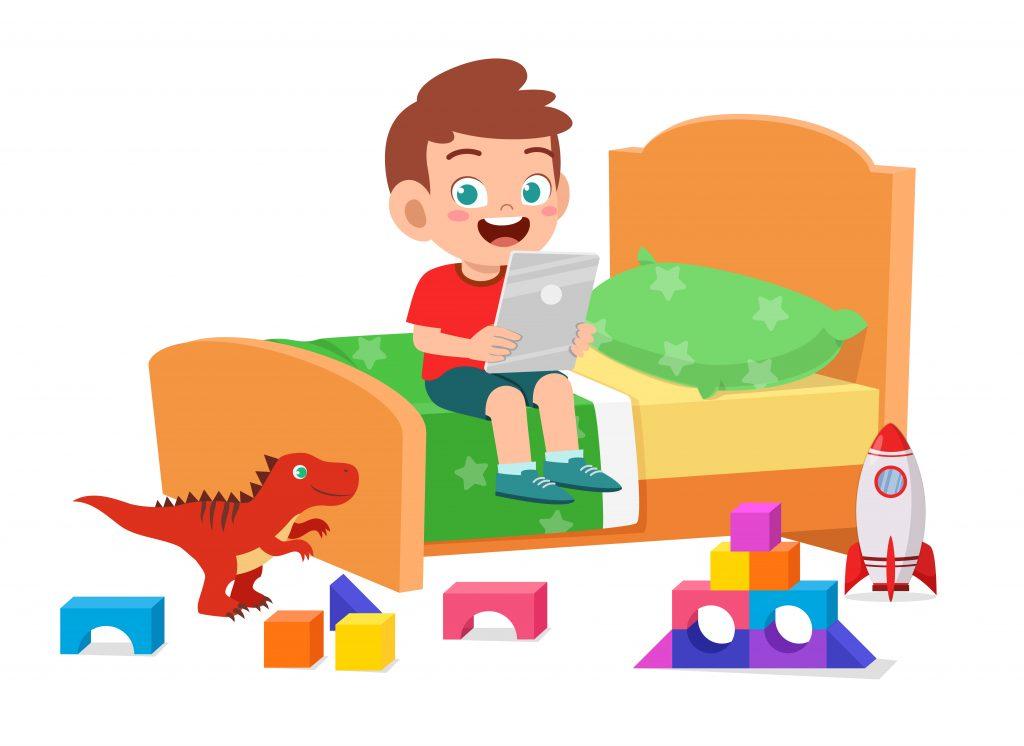 grafika chłopiec z tabletem siedzący nałóżku wokół którego leżą zabawki
