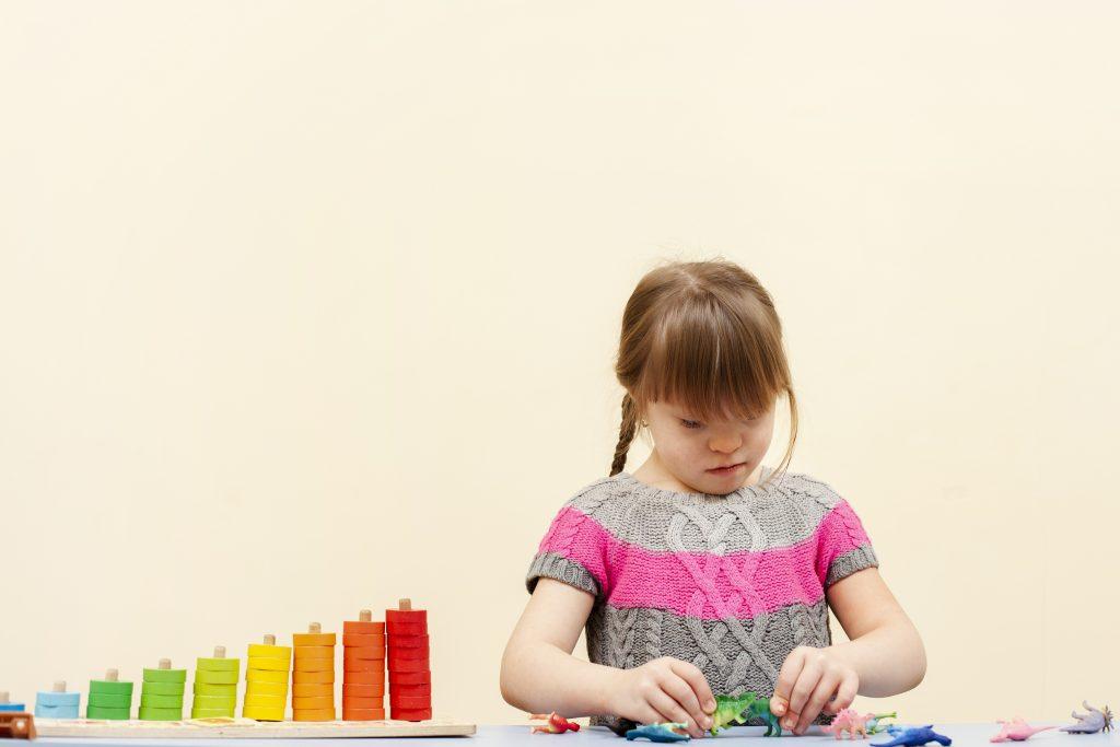dziewczynka z niepełnosprawnością bawiąca się figurkami dinozaurów