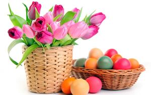 kosz z tulipanami obok koszyszka z kolorowymi pisankami