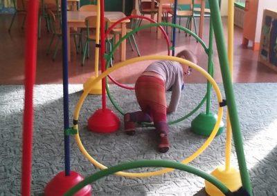 dziecko przechodzące przez kolorowe obręcze podczas terapii SI