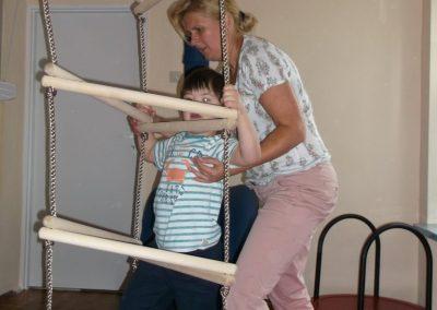 dziecko wspinające się na drabinkę przytrzymywane przez terapeutę podczas terapii SI