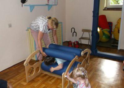 terapeuta ćwiczący z dwójką dzieci na przyrządzie do terapii SI