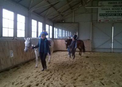 dzieci na koniach w hali jeździeckiej