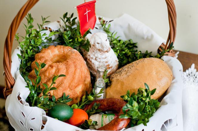 Koszyk wielkanocny wyłożony białą serwetką i bukszpanem. W środku babka wielkanocna, baranek z flagż Jezusa Zmartwychwstałego, pisanka, wędlina i czekoloadowe jajka.