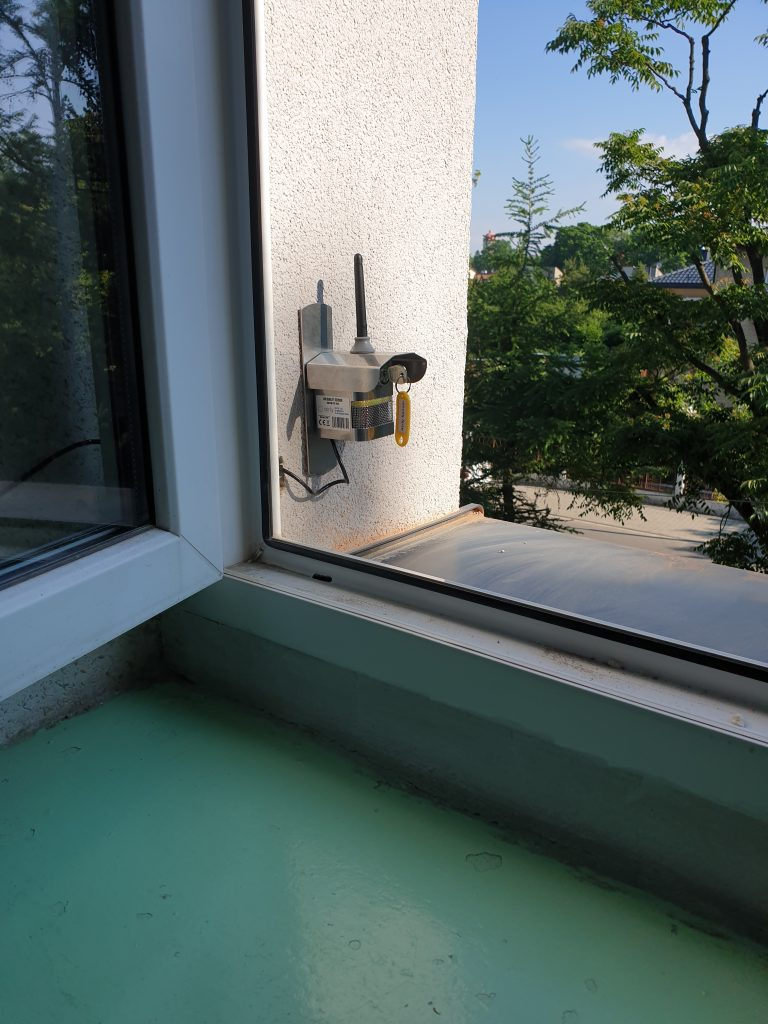 Otwarte okno, na elewacji, na zewnątrz zamontowany czujnik.