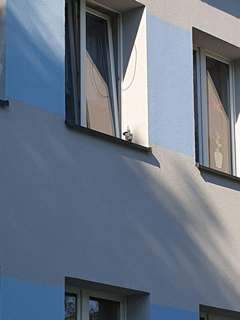 Elewacja przedszkola z widocznym oknem na pietrze, przy którym zamontowany jest czujnik smogu.